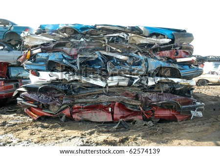 Damaged squashed cars in a junk yard - stock photo