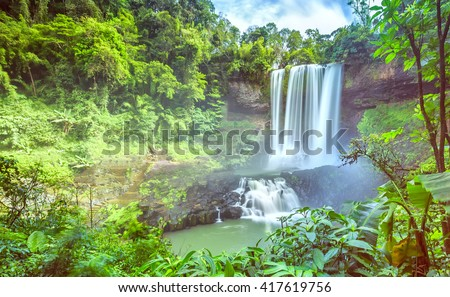 Dambri waterfall on summer days with over seventy meters high with high pouring down valley to create a lot of fog blurred in conserving native forests in Lam Dong, Vietnam - stock photo