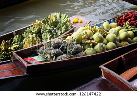 Damnoen Saduak Floating Market in Thailand with fresh fruit on display. - stock photo