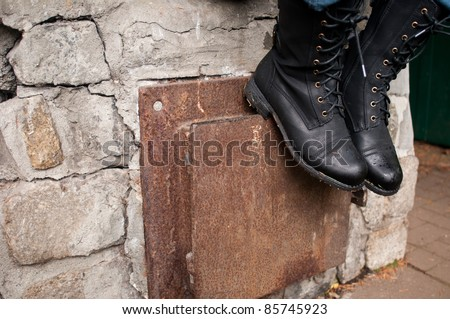 Damp Combat Boots Resting on Stone Fireplace - stock photo