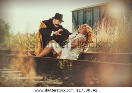 Damsel in distress woman tied up on railway line - stock photo
