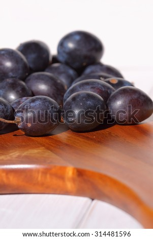 Damsons on wooden chopping board.