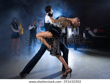 Dance couple dancing on the background of the musicians - stock photo