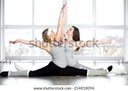 Dance lesson. Professional dancers practice, group of two sporty girls stretching, doing splits, exercises for flexibility, warming up in class - stock photo