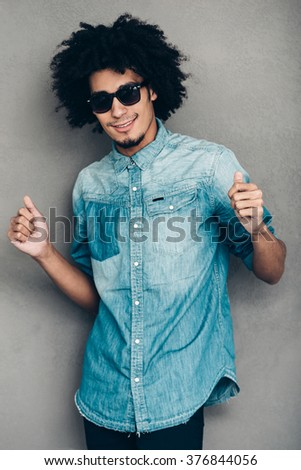 Dance like nobody sees. Confident young African man in sunglasses dancing and looking at camera with smile while standing against grey background - stock photo