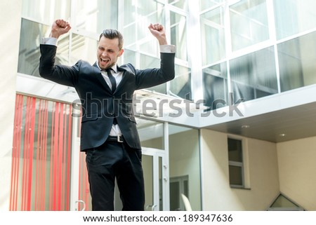 Dance success. Successful confident businessman celebrates his success. Young man formal wear his hands up and rejoice.