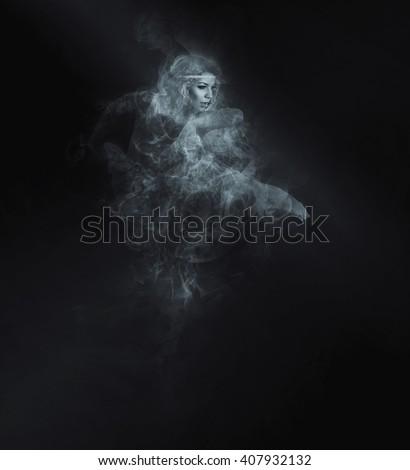 Dancer from smoke on the dark background - stock photo