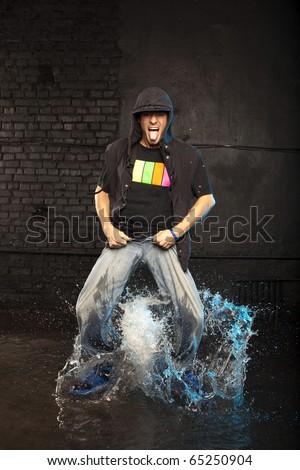 Dancer in aqua studio showing his tongue - stock photo