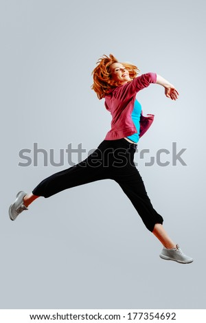 Dancer jumping against an isolated gray background