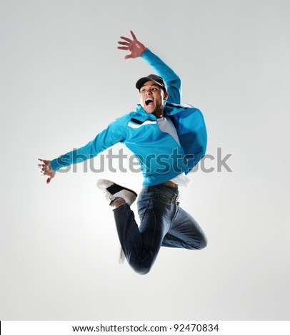 dancer jumps into the air and holds a pose, motion, movement and emotion all captured in this image - stock photo