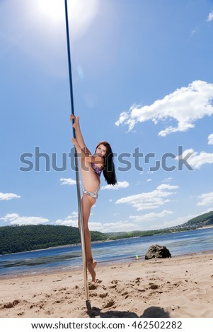 dancer pylon shows stretching on sunny beach against blue sky background