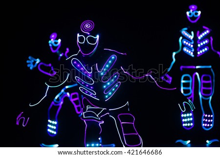 dancers crew in led suits on dark background, colored show