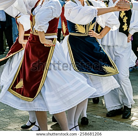 Dancers in traditional costumes who perform the movements of a serbian dance. - stock photo