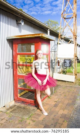 Dancing Ballerina Stands Next To A Vintage Red Telephone Box In A Communications Concept - stock photo