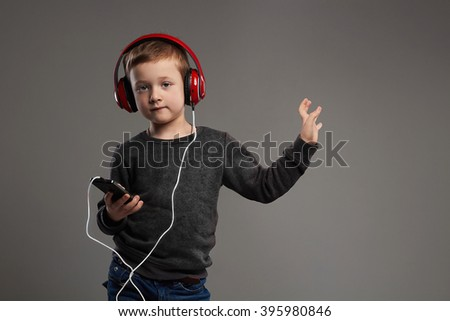 dancing child.little boy in headphones.fashionable kid listening music - stock photo