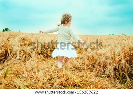 dancing child nostalgic in field - stock photo
