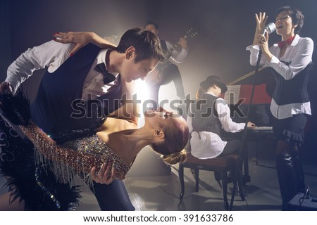 Dancing couple on background jazz orchestra - stock photo