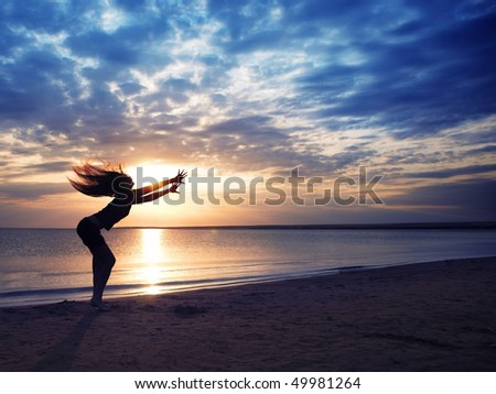Dancing dynamic woman at the beach during sunset - stock photo