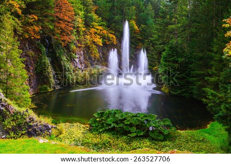 Dancing fountain in a quiet pond, surrounded by pine forest.  Butchart Gardens on Vancouver Island, Canada - stock photo