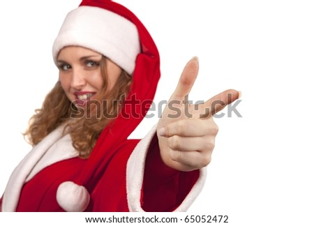 Dancing girl in santa suit is pointing her finger at the camera and looking with a smile. Isolated on white. (Focus on her finger) - stock photo