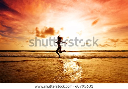Dancing girl on a tropical beach under the sky at sunset - stock photo