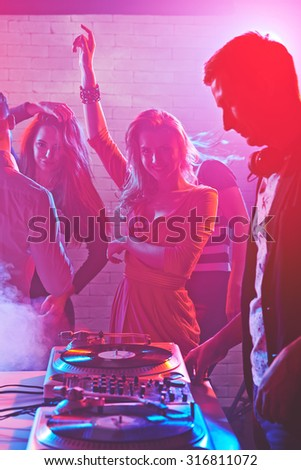 Dancing girls enjoying party by turntables of deejay adjusting sound - stock photo