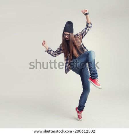 Dancing hipster girl in glasses and black beanie on the grey studio background - stock photo
