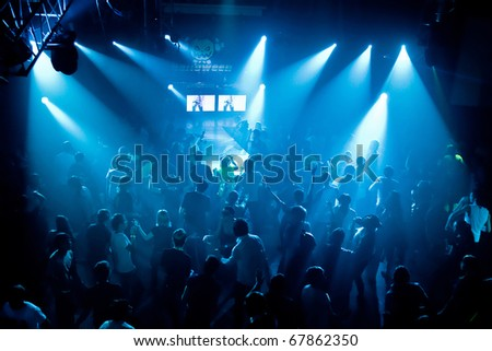 Dancing people in an underground club, blue stage light. - stock photo