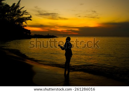 dancing woman at sunset on the beach - stock photo