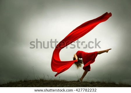 Dancing woman with fabric in red dress .