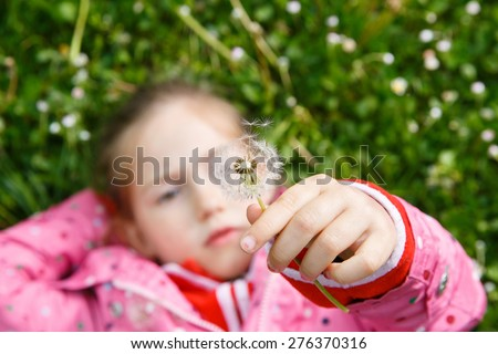 Dandelion seed head with beautiful little girl lying in grass in the background, enjoying nature and its serenity. Natural childhood concept.  - stock photo
