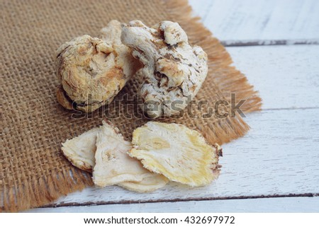 dang gui (angelica sinensis) and dang gui ginseng slice on wooden background, traditional chinese herbal medicine. - stock photo