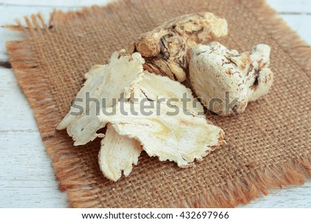 dang gui (angelica sinensis) with dang gui ginseng slice on wooden background, traditional chinese herbal medicine. - stock photo