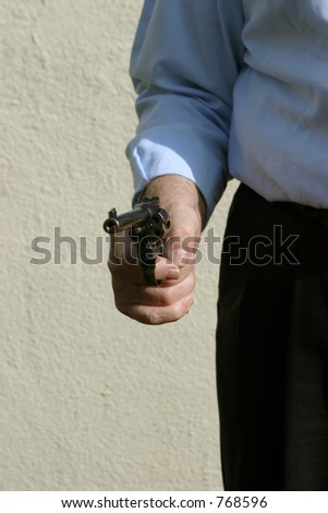 Danger, a hand gun pointed at You the viewer