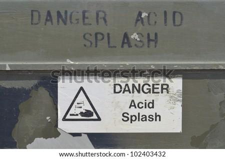Danger Acid Splash label and stenciled onto camouflaged vehicle. - stock photo