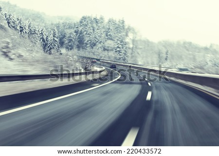 Danger and fast turn at the icy snow road. Motion blur visualizies the speed and dynamics. - stock photo