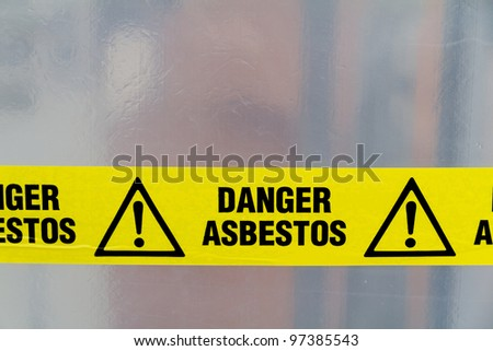 Danger Asbestos yellow warning tape close up - stock photo