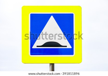 Danger bump road sign against cloudy sky - stock photo