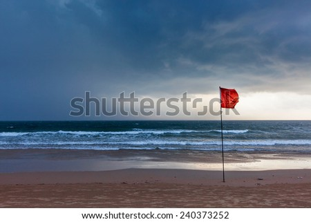 Danger concept background - severe storm warning flags on beach. Baga, Goa, India - stock photo