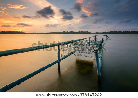 Danger Deep Water sign fitted to jetty rail with sunset view - stock photo