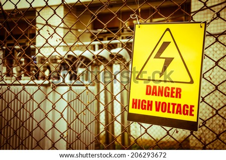 Danger high voltage warning sign on a fence in transformer station. Processed with vintage style. - stock photo