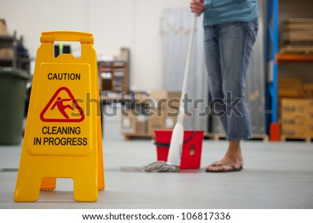 Danger Sign 'Caution Cleaning in Progress, with blurred background of warehouse and cleaner and copy space. - stock photo