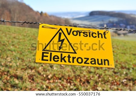 Danger Sign Electric-Fence, Barbed Wire, surrounding a Pasture