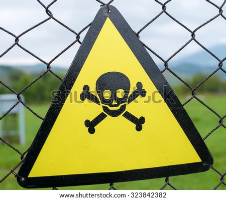 Danger sign (skull and bones) on the metal mesh. Close up. - stock photo