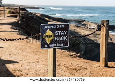 Danger sign with trail in background at Sunset Cliffs in San Diego, California.  - stock photo