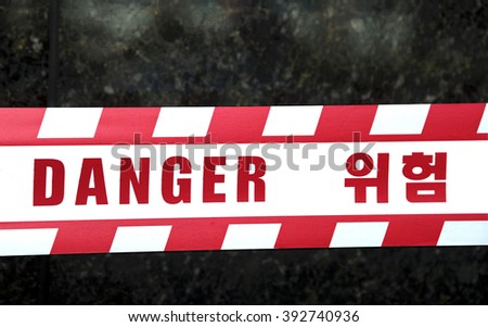 Danger tape with text in English and Korean language - stock photo