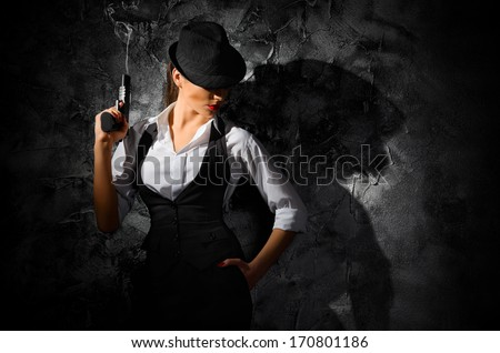 Dangerous and beautiful criminal girl with gun on grey wall - stock photo