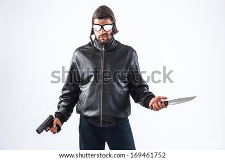 Dangerous and violent criminal wearing cap and glasses is holding a gun and a knife in his hands - isolated on white - stock photo