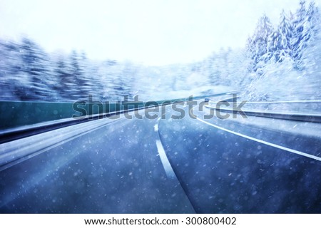 Dangerous blurred highway winter driving. Winter snowy conditions on the highway. Motion blur visualizies the speed and dynamics. - stock photo