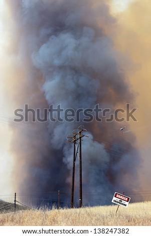 Dangerous brush fire with water dropping helicopter and danger sign - stock photo
